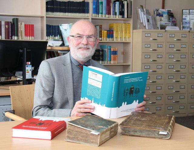 Autor Dr. Hans-Helmut Görtz bei der Präsentation seines Buches im Bistumsarchiv in Speyer. Auf dem Tisch die beiden Original-Kirchenbücher, die er für seine Studie ausgewertet hat, sowie sein Buch aus dem Jahr 2015.
